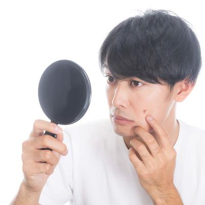 「手鏡でニキビを確認する男性」の写真素材