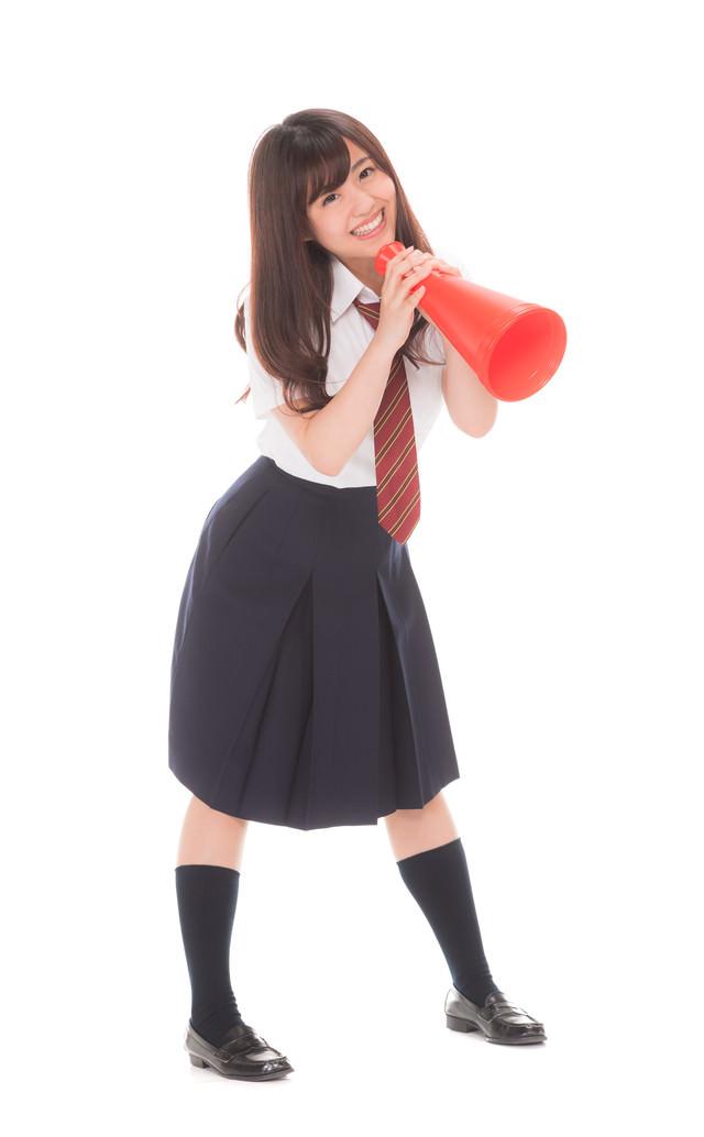メガフォンで声援する制服姿の女子高生(マネージャー)の写真