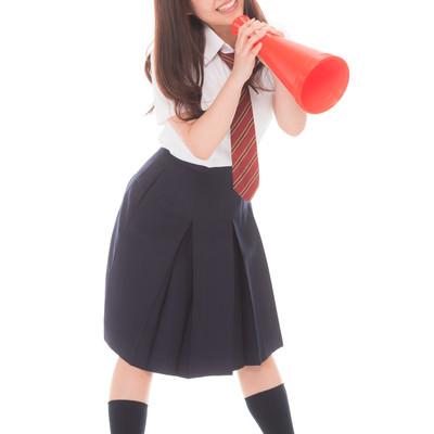 「メガフォンで声援する制服姿の女子高生(マネージャー)」の写真素材