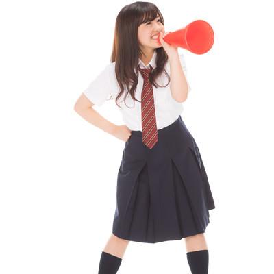 メガホンで大声を出す女子高生の写真