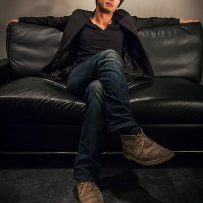 「ソファーの上に仰け反る偉そうな男性」の写真素材