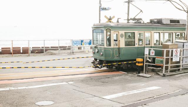鎌倉高校前駅の踏切を走行する江ノ電の写真