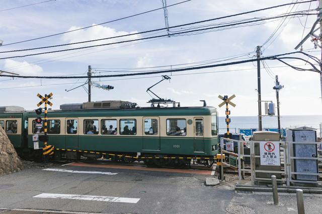 アニメのワンシーンで登場しそうな鎌倉高校前駅の踏切と江ノ電の写真
