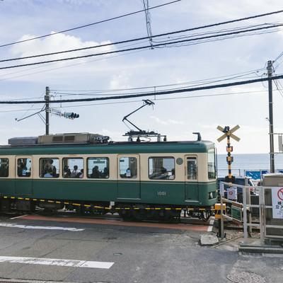「アニメのワンシーンで登場しそうな鎌倉高校前駅の踏切と江ノ電」の写真素材