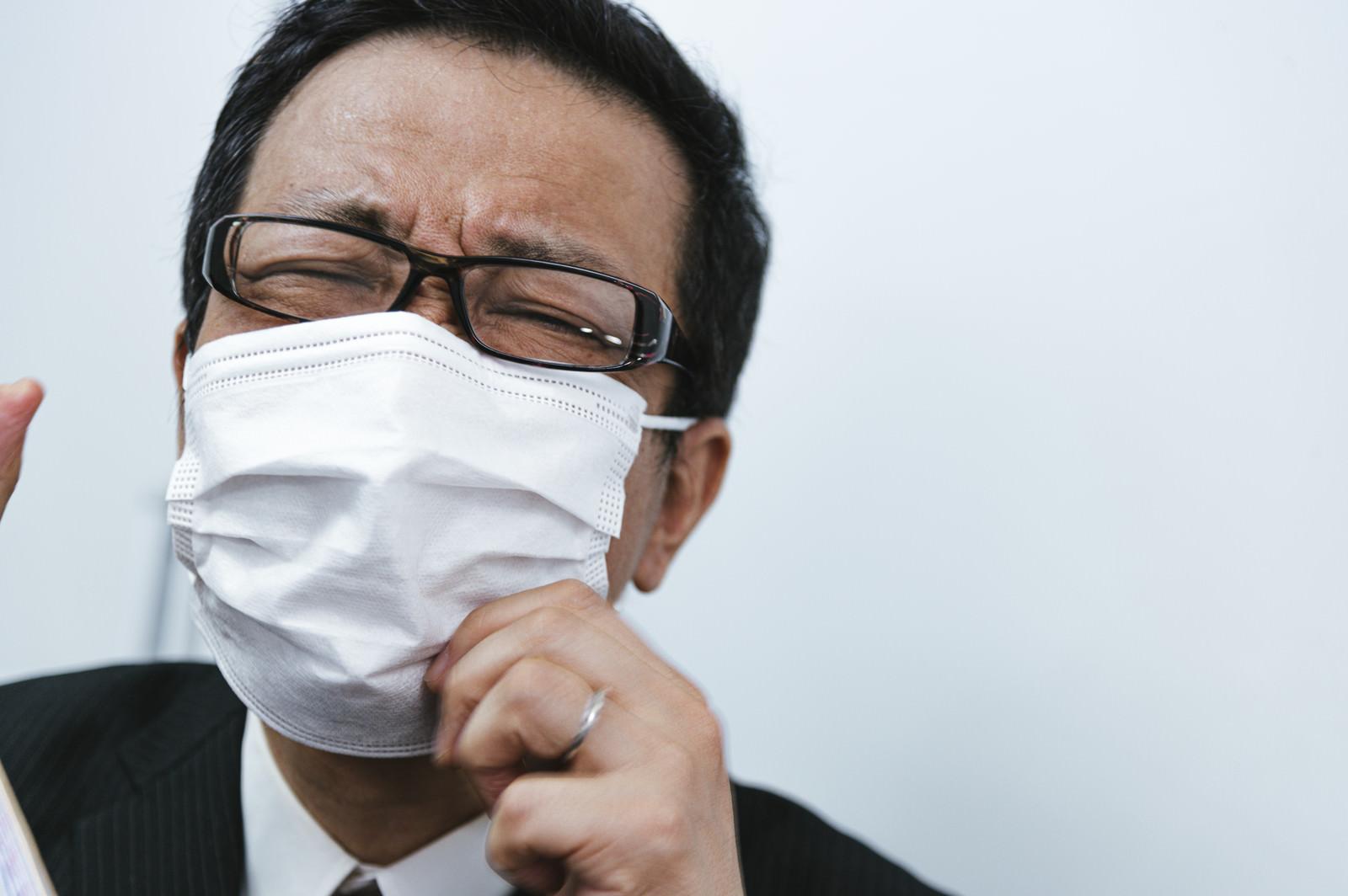 「マスクが息苦しくて耐えきれいない会社員」の写真[モデル:のせさん]