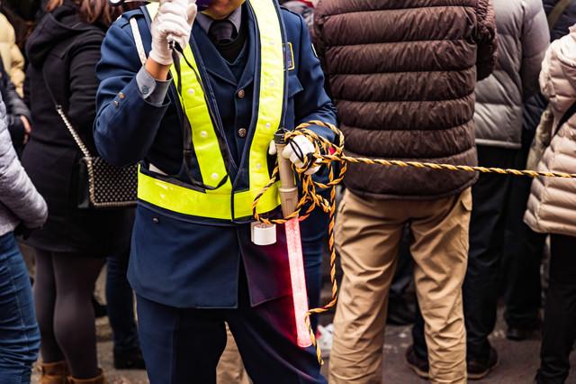 ロープを持って交通整理する警備員の写真