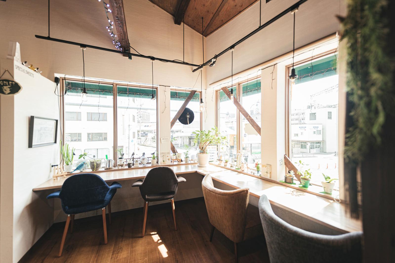 「陽の光が入るカフェの窓辺席」の写真