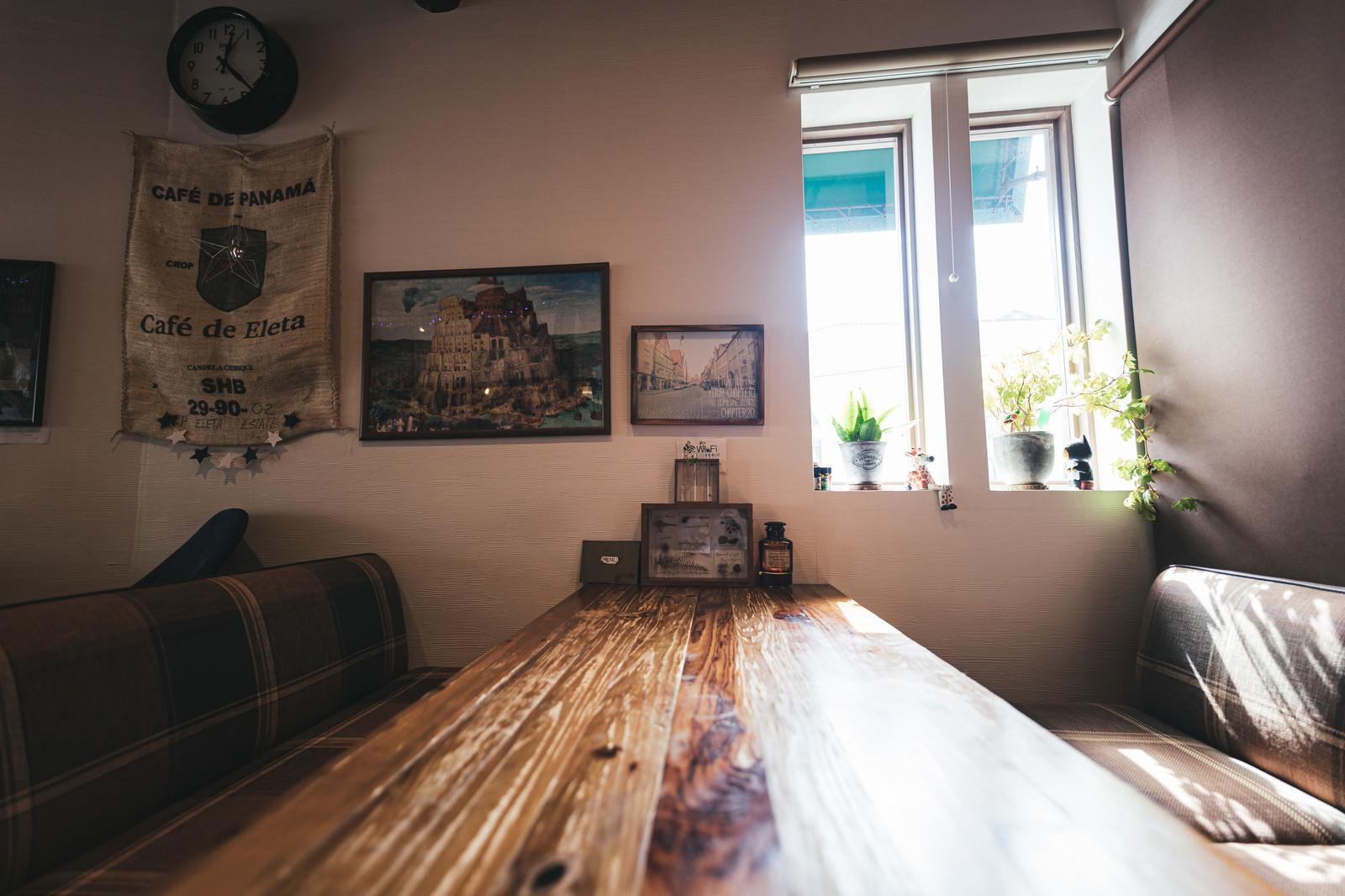 「陽の光差し込めるカフェのテーブル」の写真