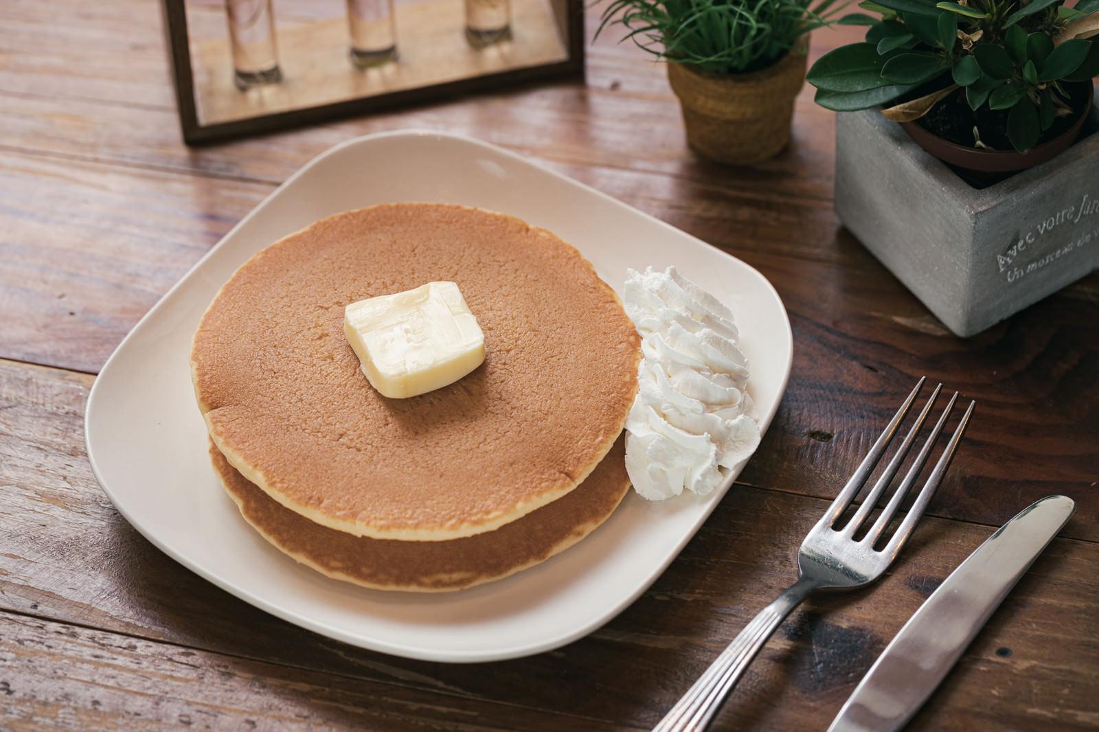 「バターとホイップクリームが添えられたパンケーキ」の写真