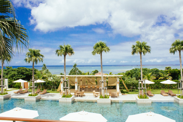 沖縄の青い海とヤシの木が並ぶリゾートの写真
