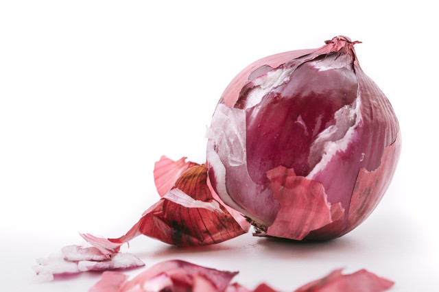 表皮を剥かれたボロボロな紫玉葱の写真