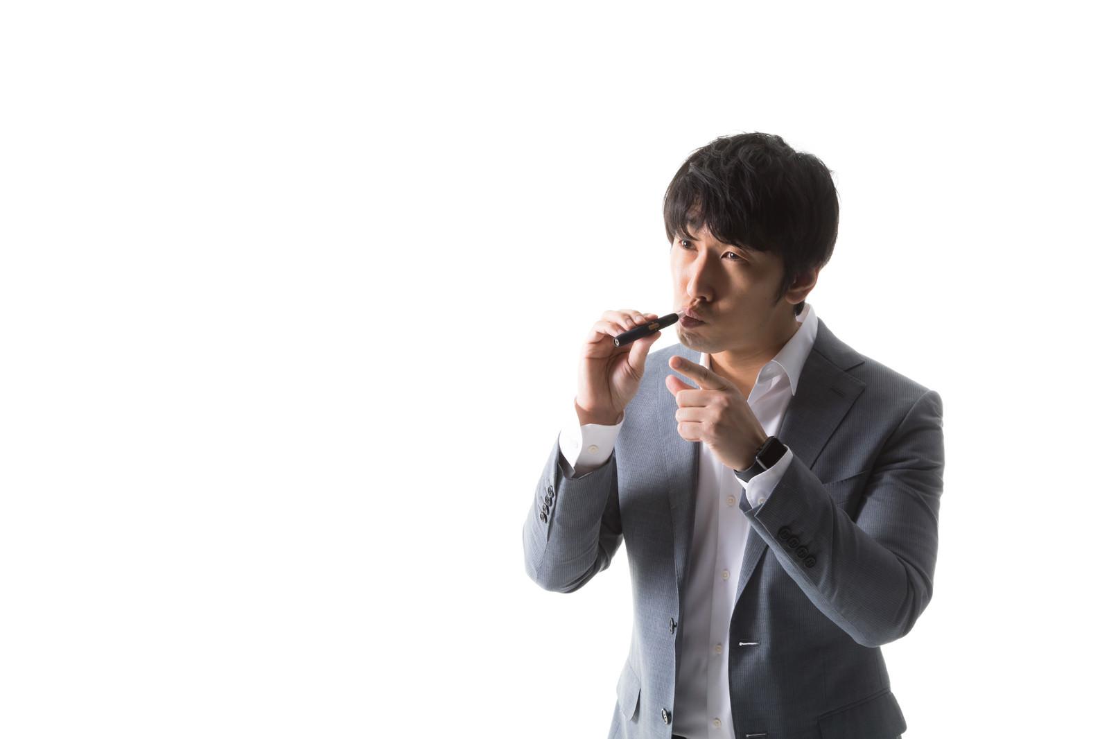 「加熱式たばこを吸いながら指差し確認をする男性」の写真[モデル:大川竜弥]