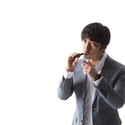 加熱式たばこを吸いながら指差し確認をする男性の写真