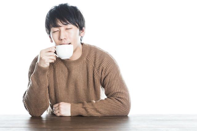 温かい紅茶を飲んで幸せそうな男性の写真