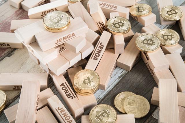 崩れ落ちたジェンガとビットコインの写真