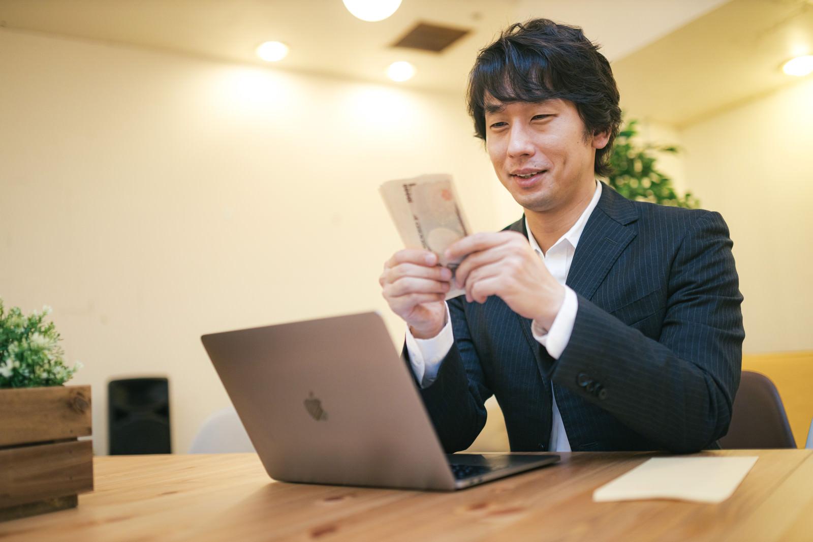 「特別定額給付金の支給に喜ぶ男性」の写真[モデル:大川竜弥]