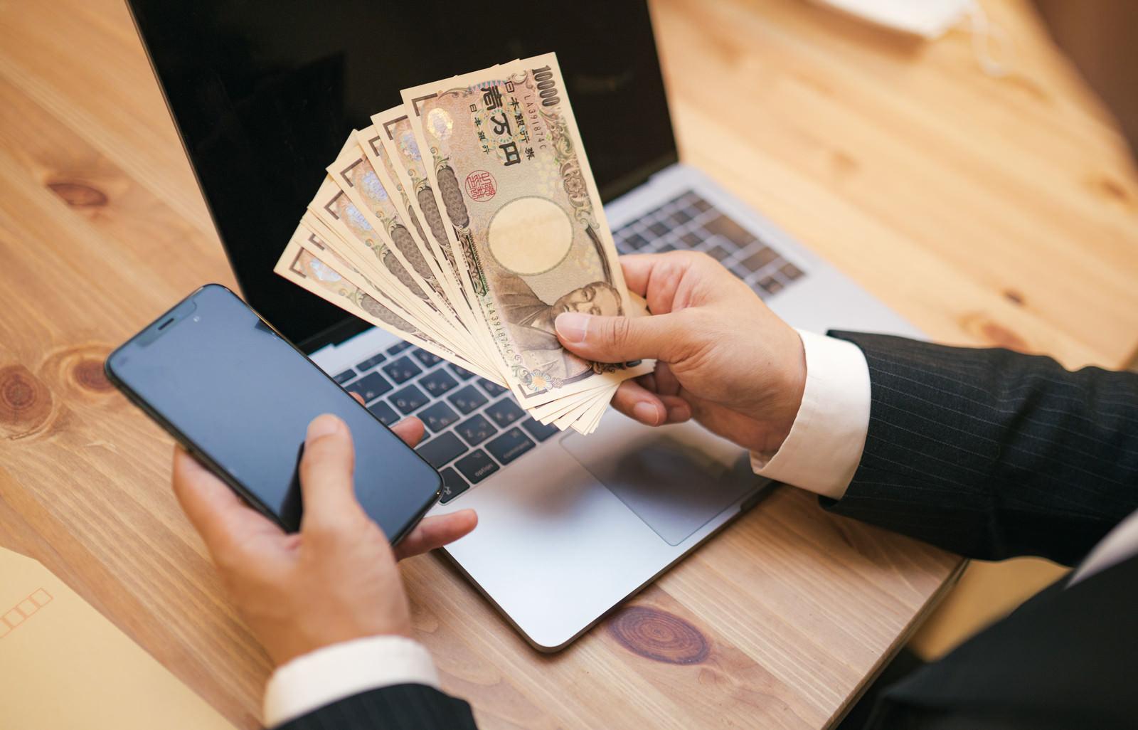 「10万円とスマートフォンとパソコン」の写真