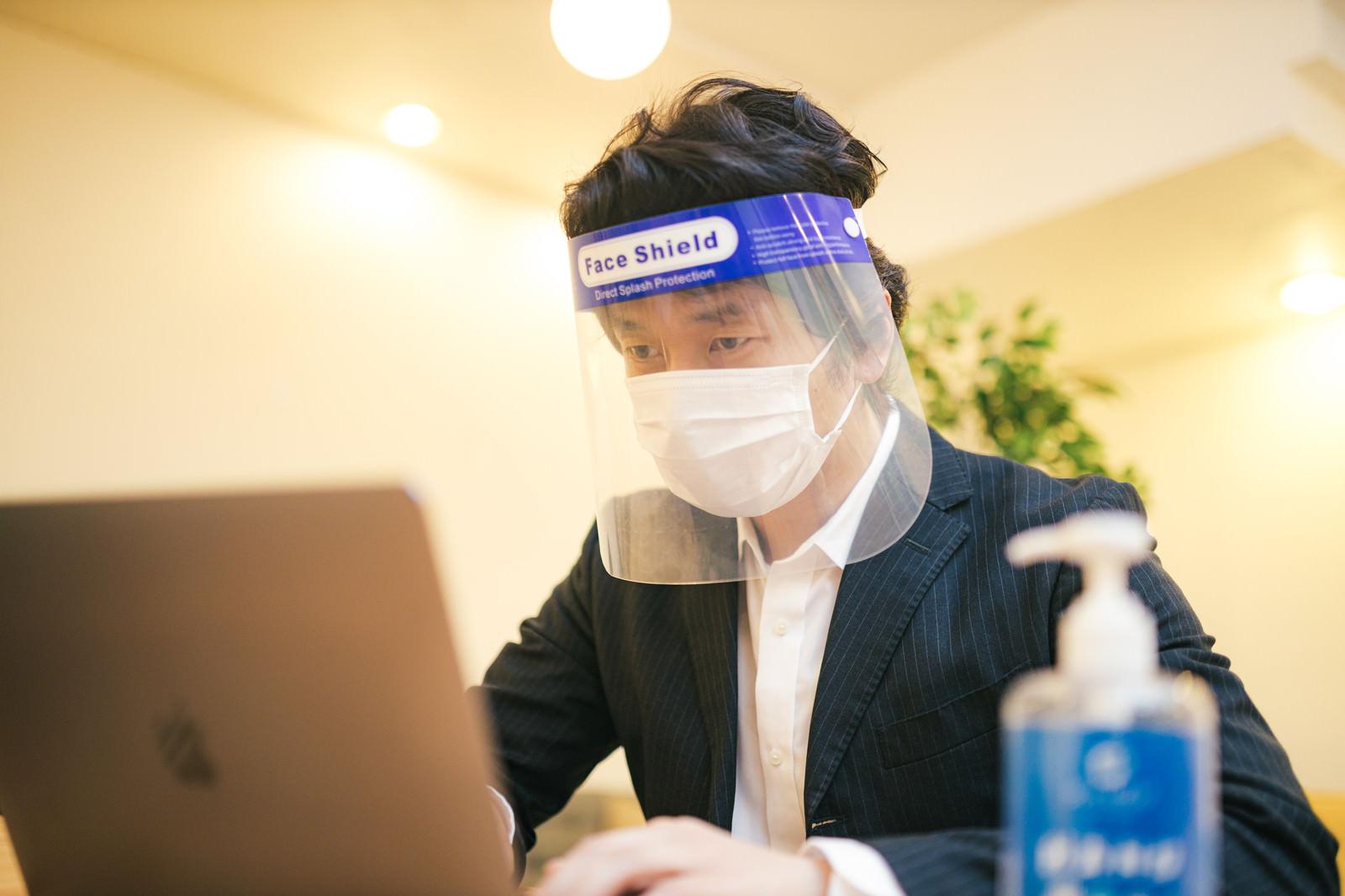 「オンライン会議中もフェイスシールドとマスクを装着する男性」の写真[モデル:大川竜弥]