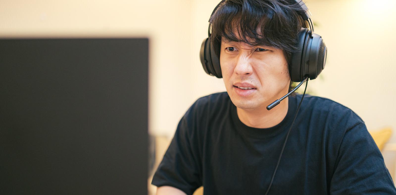 「オブジェクトを無視する仲間が多くて思うようにプレイができずイライラする男性」の写真[モデル:大川竜弥]