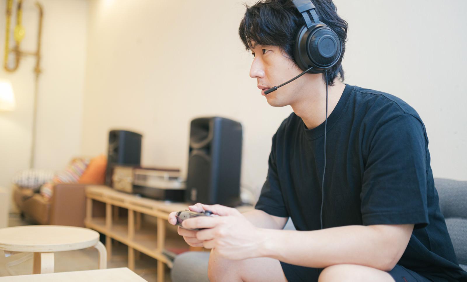 「ヘッドセットをしながらゲームに熱中する男性」の写真[モデル:大川竜弥]