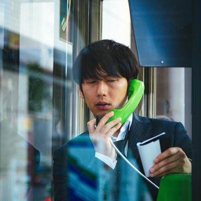 スマートフォンを忘れ電話ボックスに駆け込んだ男性の写真