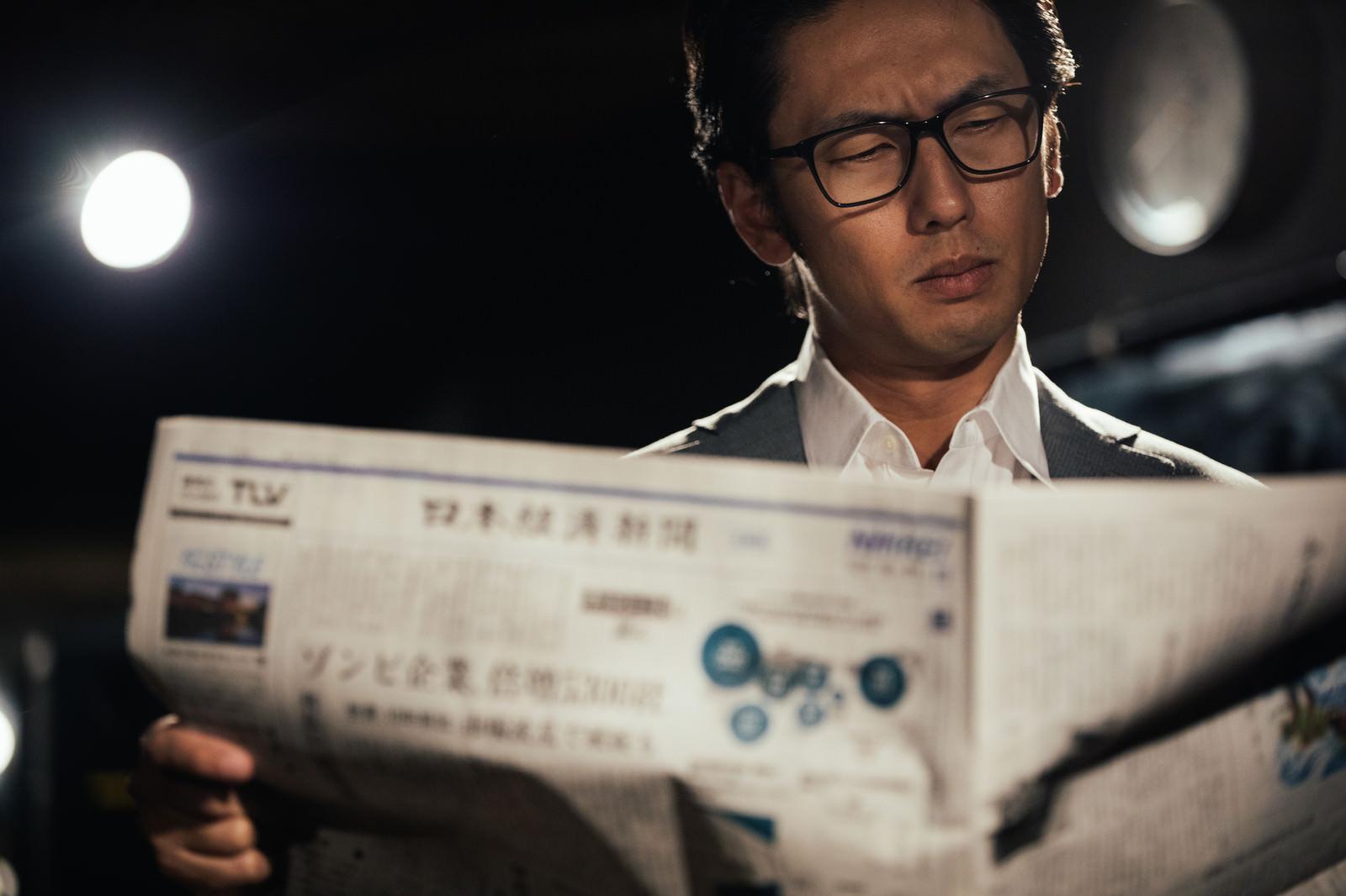 「経済新聞を広げるビジネスマン | 写真の無料素材・フリー素材 - ぱくたそ」の写真[モデル:大川竜弥]