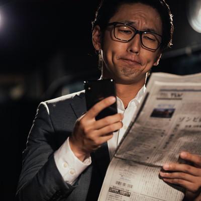 紙面と電子版を同時にチェックするビジネスマンの写真