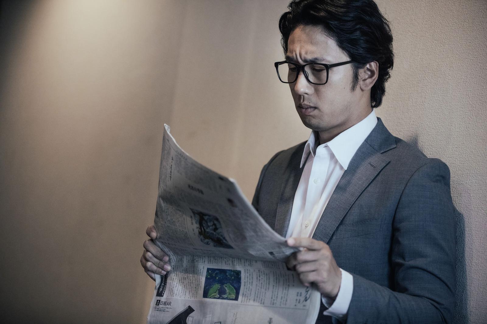 「自社のリークを紙面で知る役員」の写真[モデル:大川竜弥]