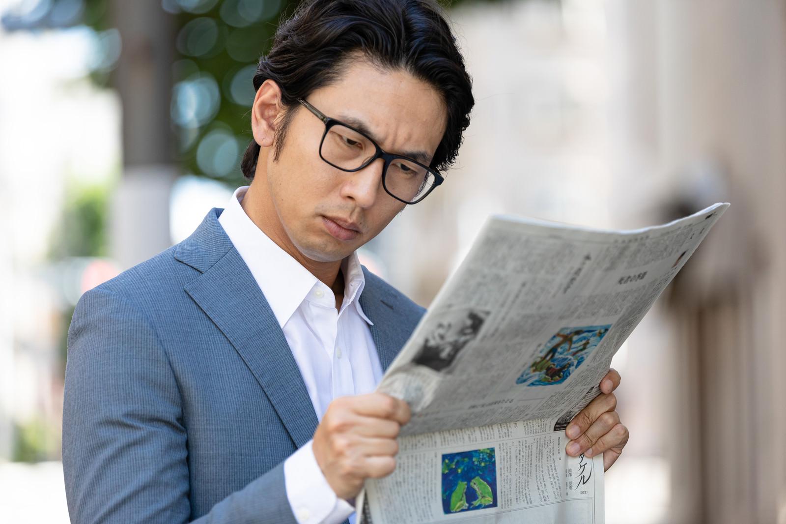 「目を凝らして紙面を読む会社員」の写真[モデル:大川竜弥]