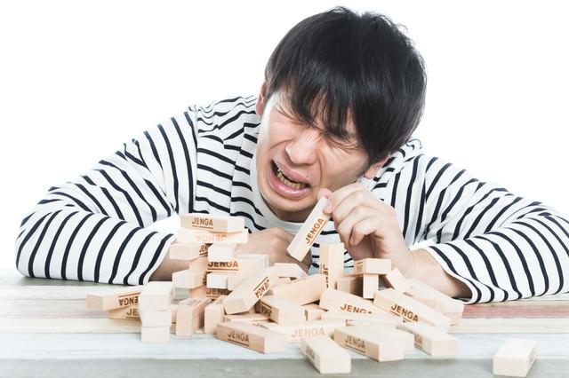 ジェンガ崩壊に泣き崩れる男性の写真