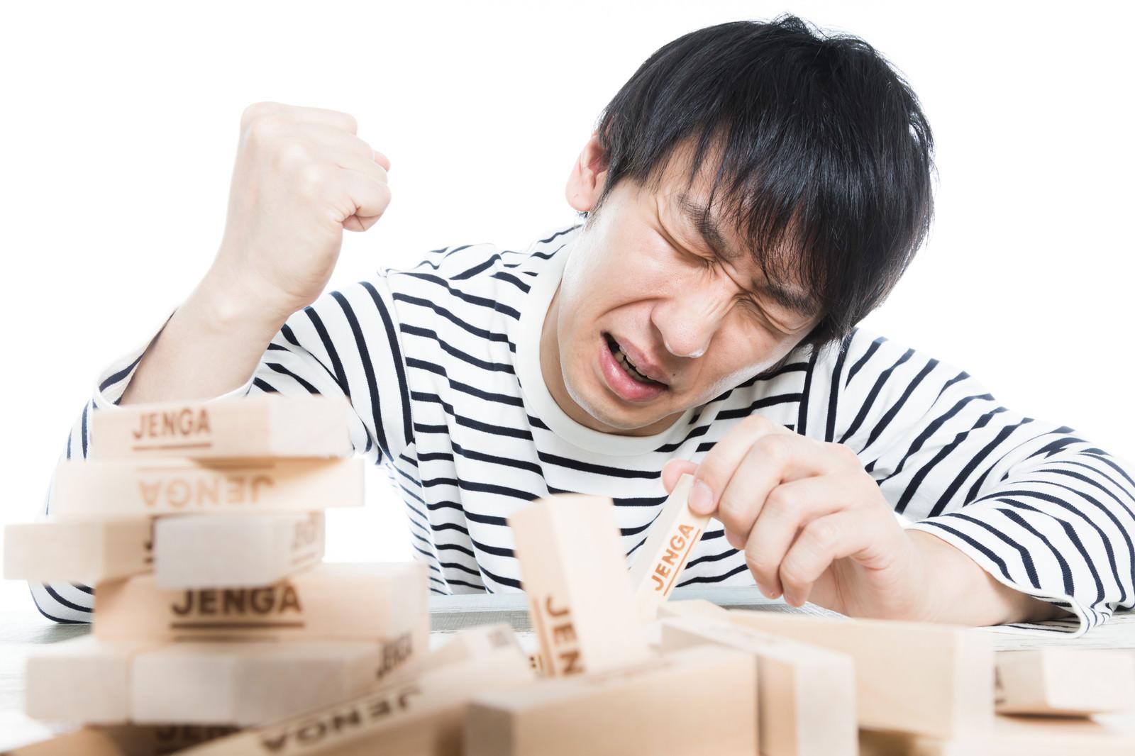 「悔しさのあまりテーブルを叩く男性」の写真[モデル:大川竜弥]
