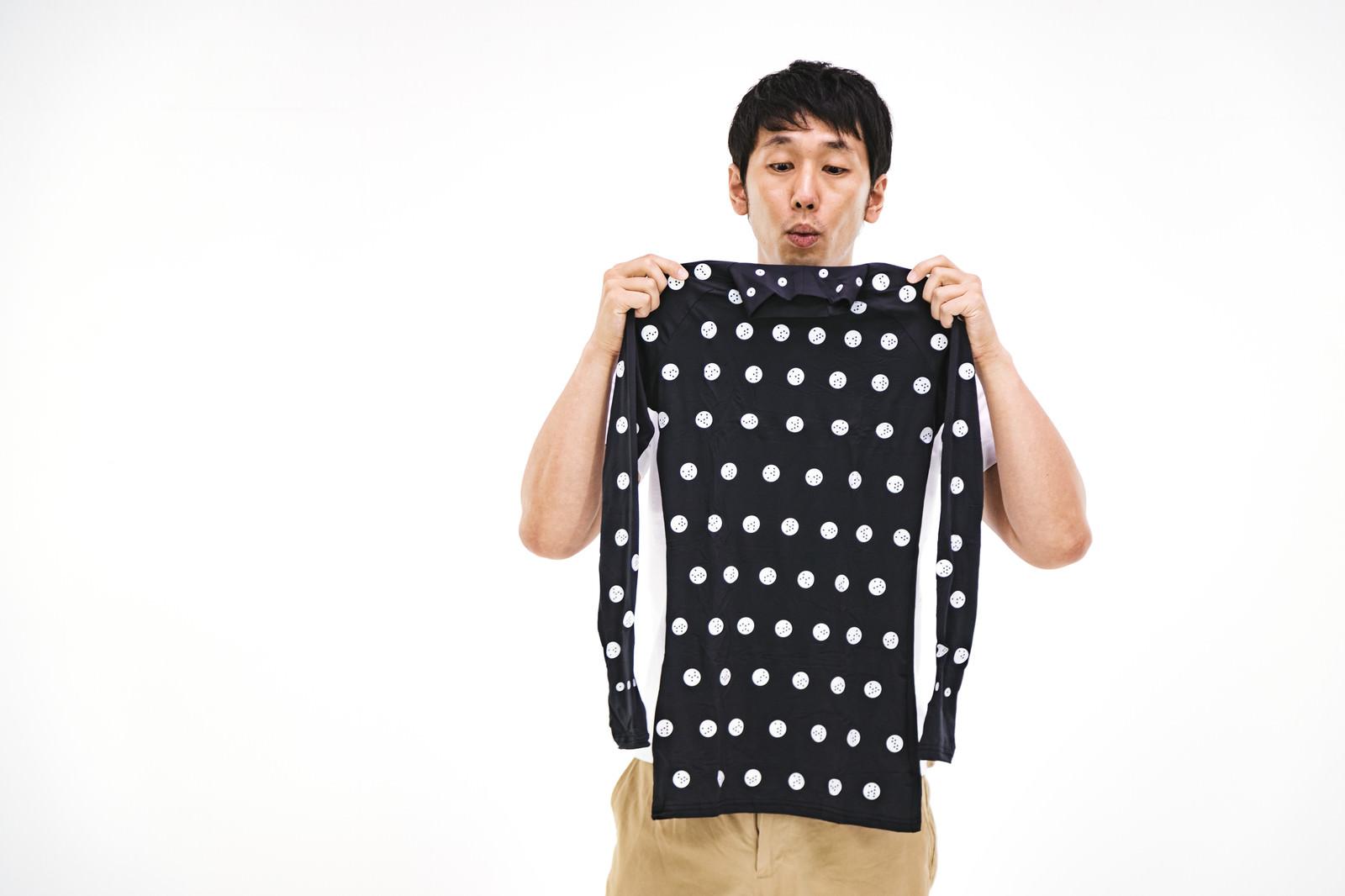 「着用前にタグの向きを確認する男性」の写真[モデル:大川竜弥]
