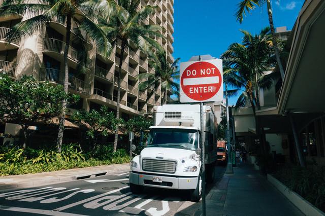 ハワイの道路標識と停車する大型トレーラーの写真