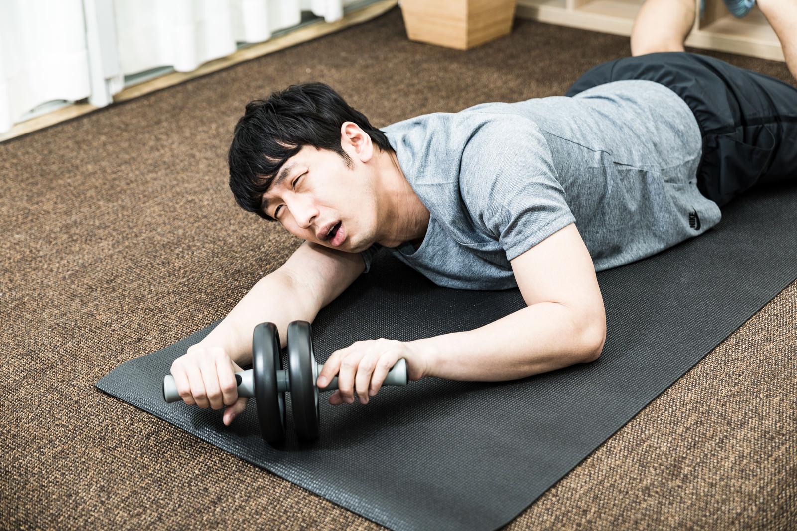 「幸福のCDをBGMに筋トレを頑張る男性」の写真[モデル:大川竜弥]