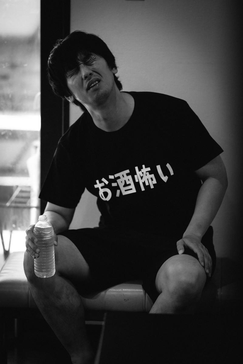 「二日酔いで飲み物が手放せない男性」の写真[モデル:大川竜弥]