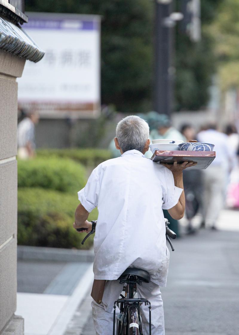 「片手で出前を運ぶ職人」の写真