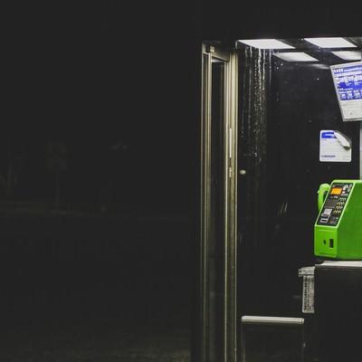 「暗闇の中の電話ボックス」の写真素材