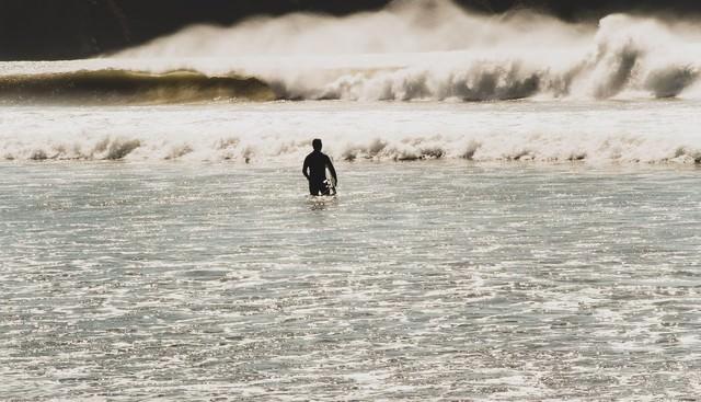 冬の海とサーファーの写真