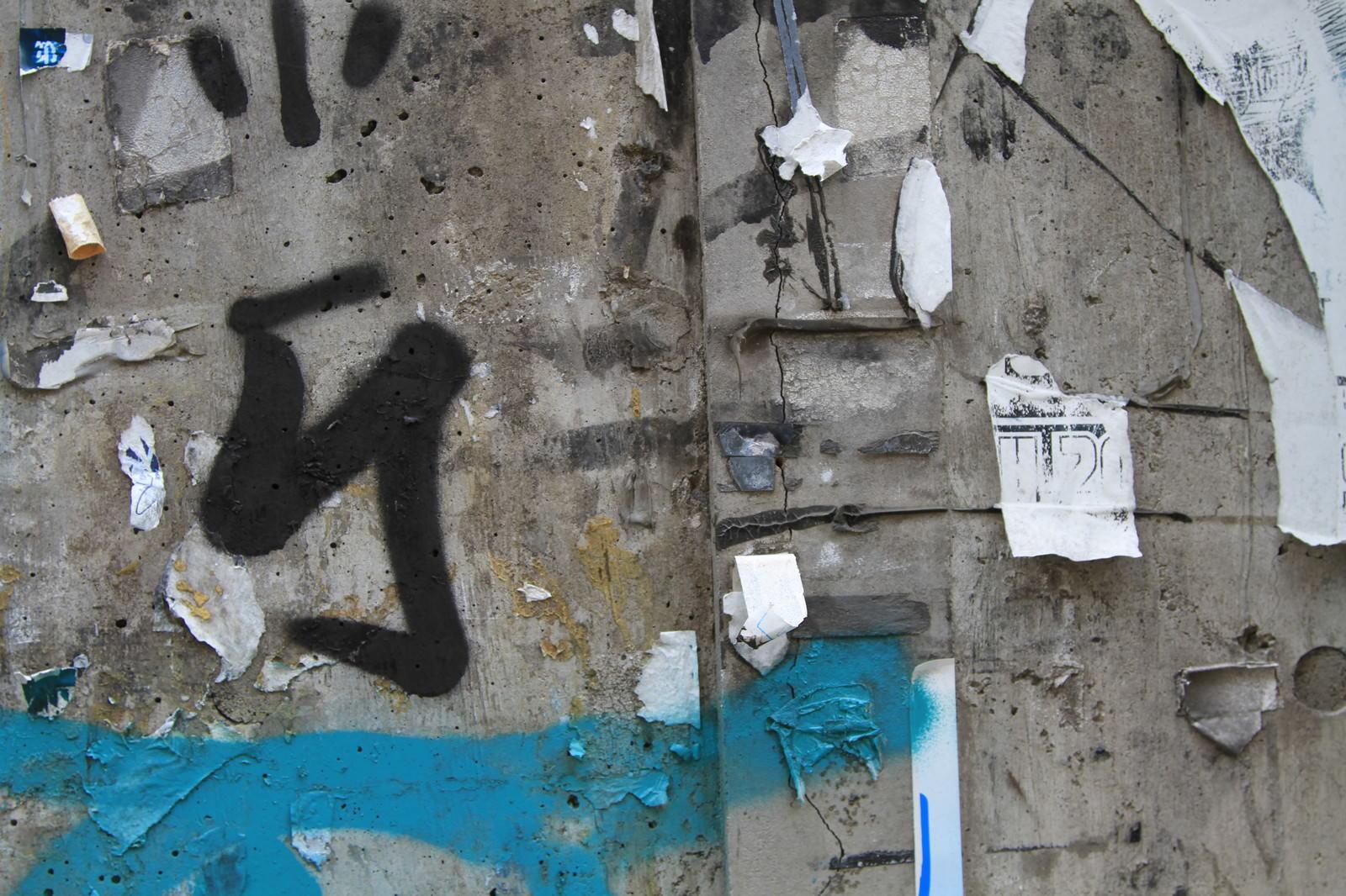 「落書きとシールが剥がされた汚い壁」の写真