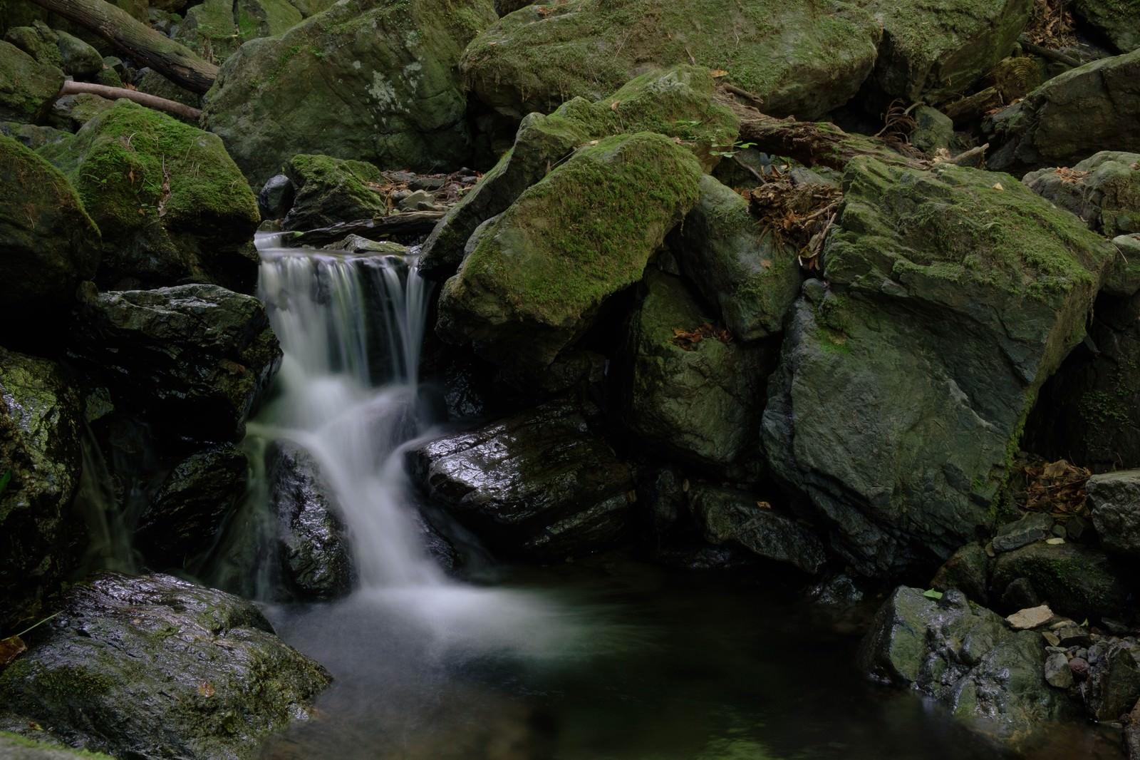 「険しい山道の岩場と小さな滝」の写真