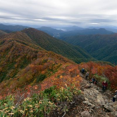 紅葉する谷川岳の稜線を歩く登山者の写真