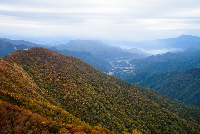 色づき始める谷川岳と眼下に広がる町の写真