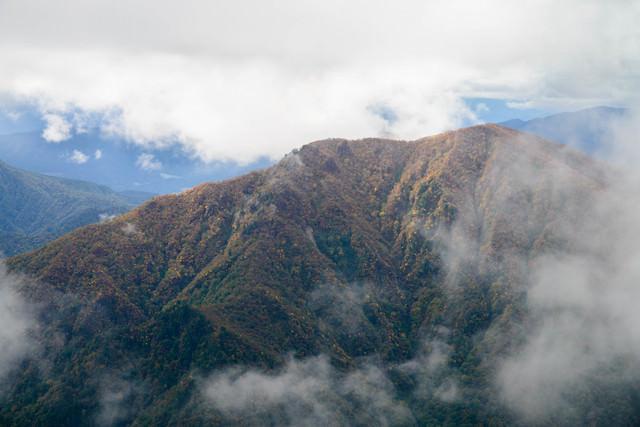 雲がかかる谷川連峰の秋の写真