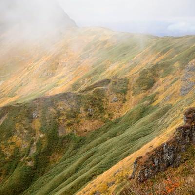 沸き立つガスと黄葉する秋の谷川岳の写真