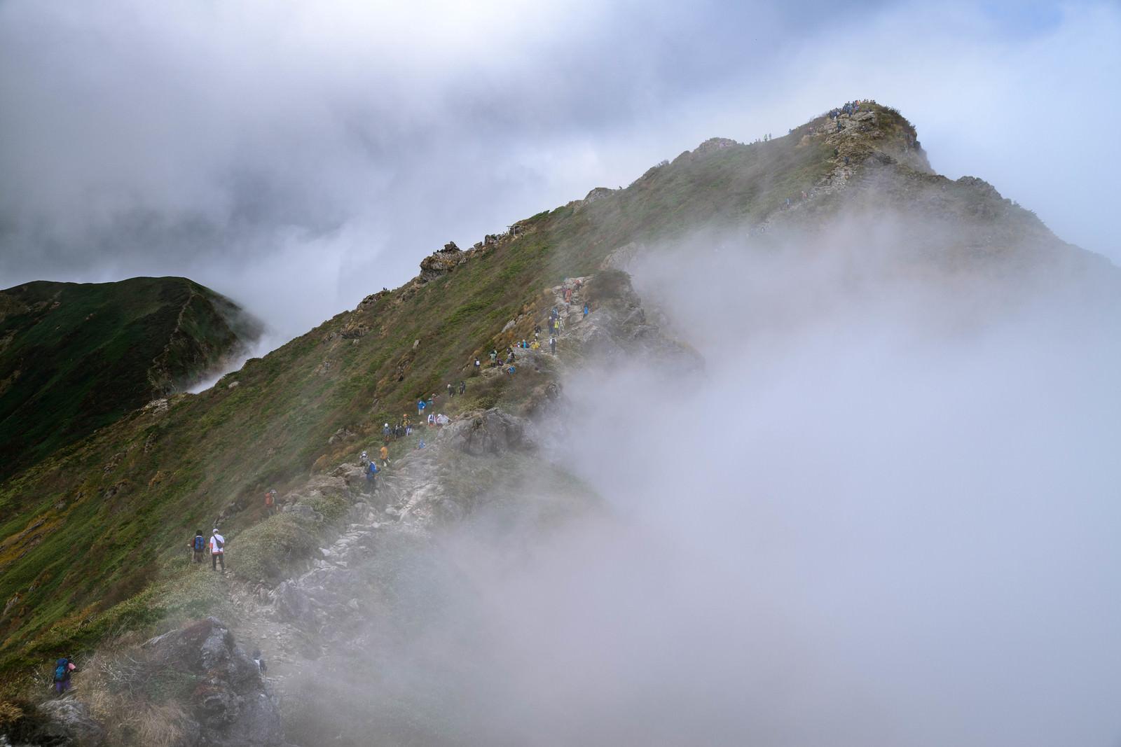 「谷川岳(オキの耳)の尾根に集まる登山者達(秋)」の写真
