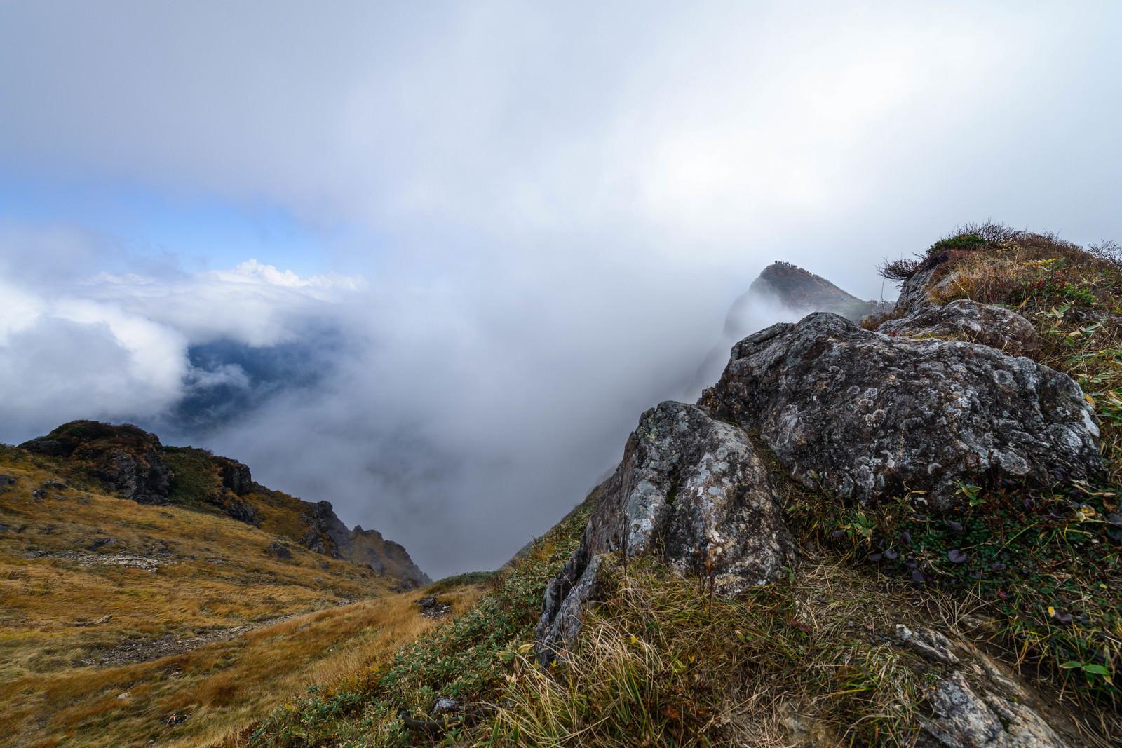「山頂に登るも雲で景観を遮られる」の写真