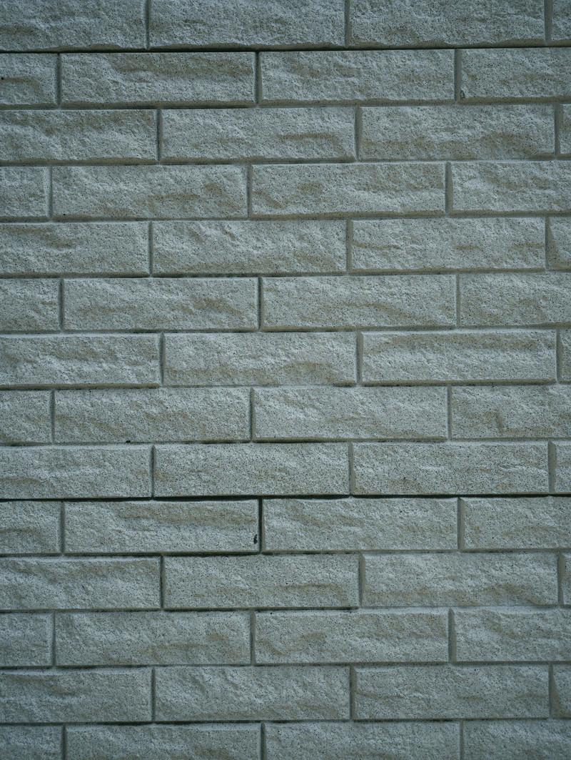 「凹凸のあるブロックタイルが敷き詰められた壁(テクスチャ)」の写真