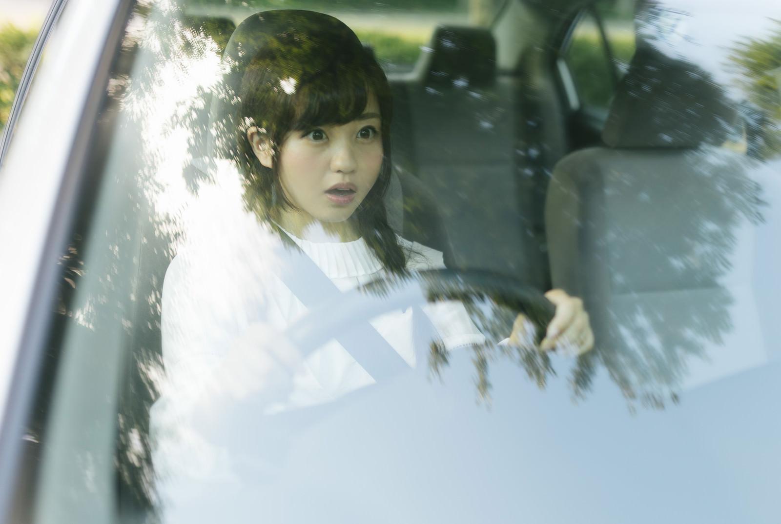 「運転中に死角から人が飛び出してきたので急ブレーキする若い女性」の写真[モデル:河村友歌]