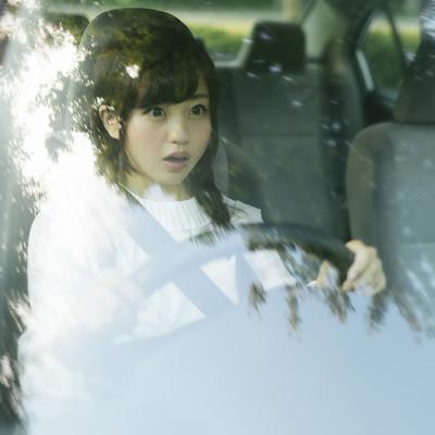 運転中に死角から人が飛び出してきたので急ブレーキする若い女性の写真