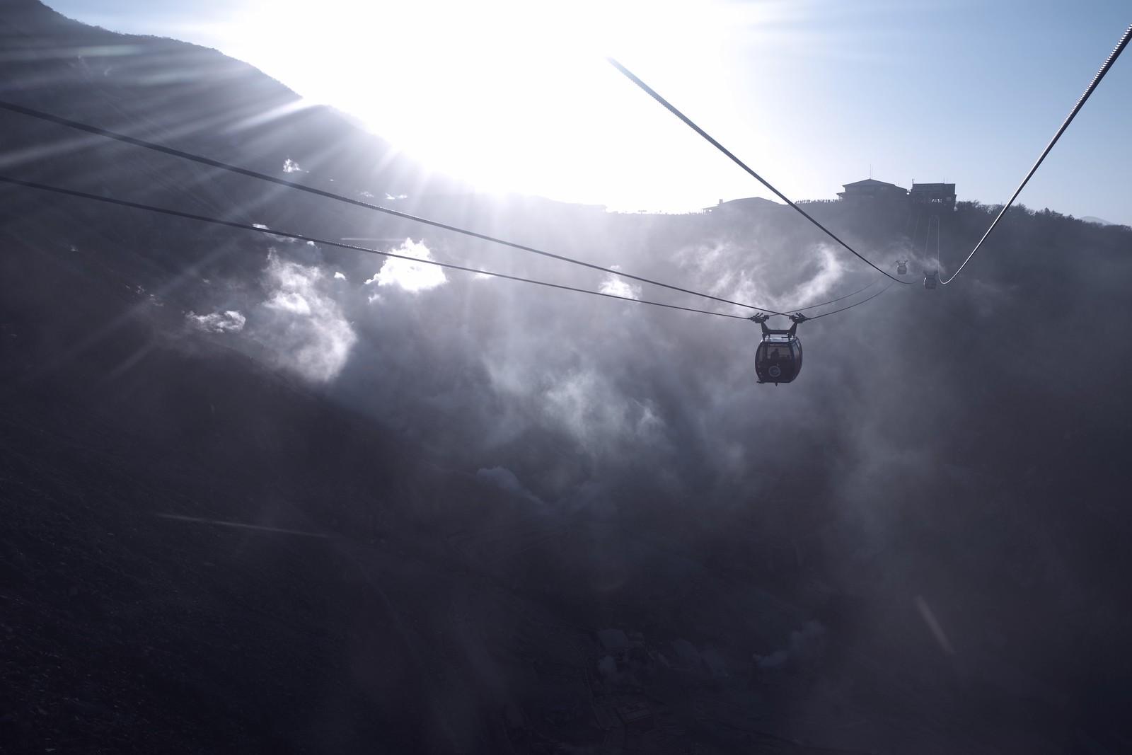「蒸気が沸き立つ大涌谷の上を走るロープウェイ」の写真